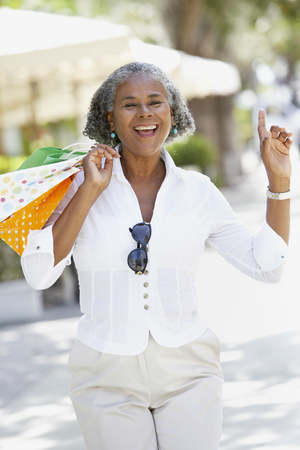 African woman carrying shopping bags and dancing LANG_EVOIMAGES