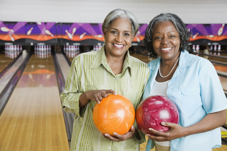 African women holding bowling balls in bowling alley
