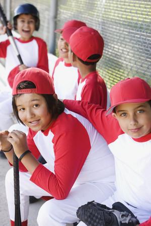 Multi-ethnic boys in baseball uniforms in dugout