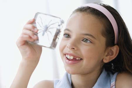 Hispanic girl looking at spider specimen in plastic LANG_EVOIMAGES
