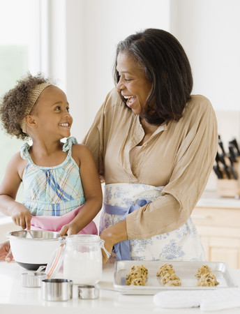 African grandmother baking cookies with granddaughter