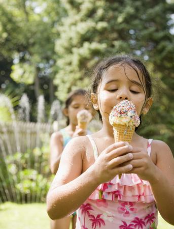 Hispanic girls eating ice cream cones LANG_EVOIMAGES