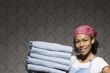 Mixed race housewife carrying stack of folded towels LANG_EVOIMAGES