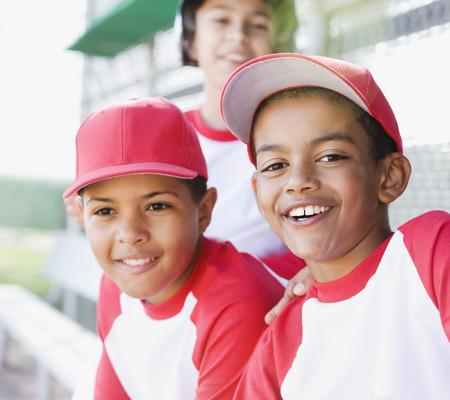Multi-ethnic boys in baseball uniforms smiling