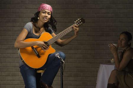 Mixed race woman playing guitar in nightclub