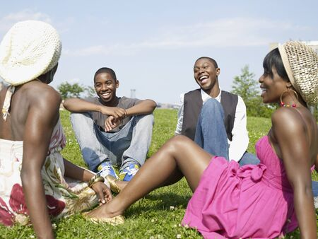 Laughing African friends sitting in park LANG_EVOIMAGES