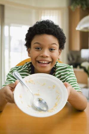 Mixed race boy holding up empty bowl