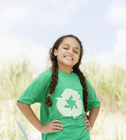 Hispanic girl on beach in t-shirt with recycling symbol LANG_EVOIMAGES