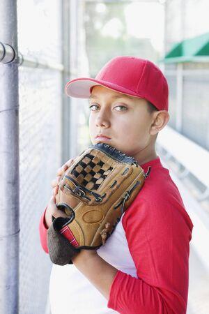 Hispanic boy in baseball uniform holding baseball glove