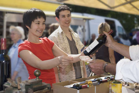 Asian couple buying wine at outdoor market
