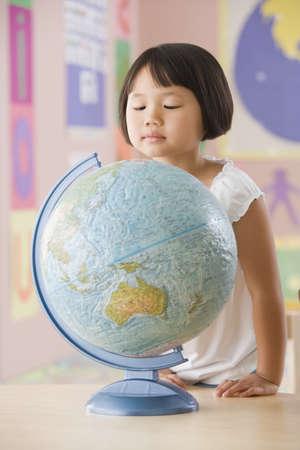 Asian school girl looking down at globe