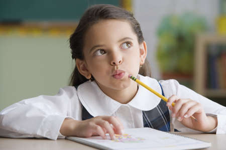 Hispanic girl thinking at desk in classroom LANG_EVOIMAGES