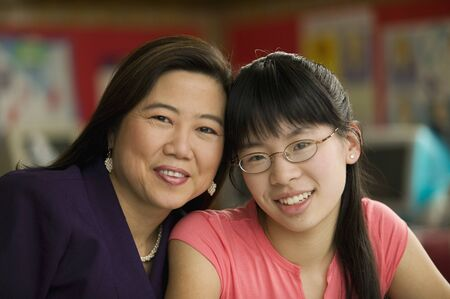 Asian teacher and student smiling