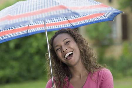 Laughing Mixed race woman holding umbrella LANG_EVOIMAGES