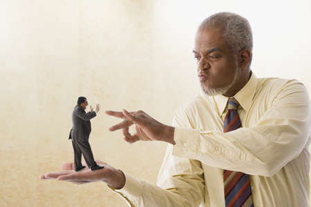 Giant businessman flicking miniature businessman LANG_EVOIMAGES