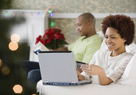 Mixed race woman buying Christmas presents online with credit card LANG_EVOIMAGES