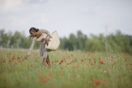 Mixed race woman picking flowers in field LANG_EVOIMAGES