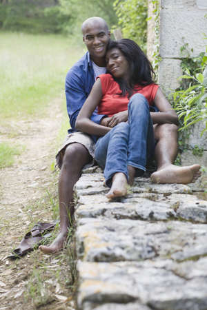 African couple cuddling outdoors