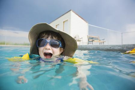 Mixed race girl wearing sunglasses in swimming pool