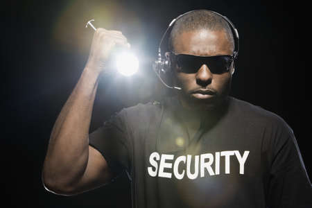 African security guard with flashlight