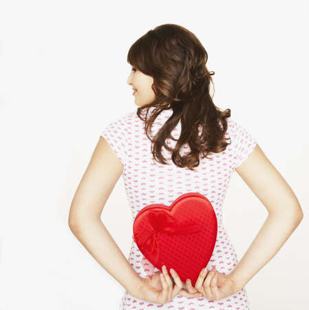 Pacific Islander woman holding heart-shaped box LANG_EVOIMAGES