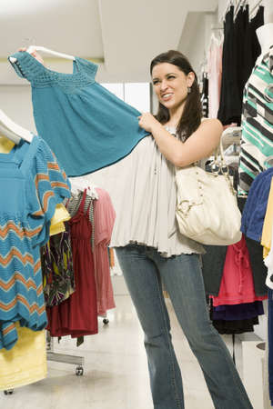 Mixed race woman holding shirt in clothing shop