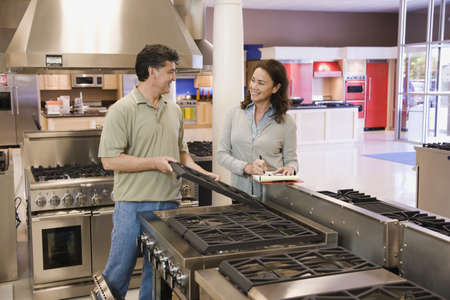 Saleswoman helping customer in appliance showroom LANG_EVOIMAGES