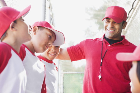 Multi-ethnic boys in baseball uniforms with coach LANG_EVOIMAGES