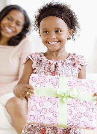 Granddaughter giving African grandmother gift LANG_EVOIMAGES