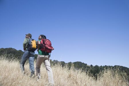 Multi-ethnic couple backpacking in rural area LANG_EVOIMAGES