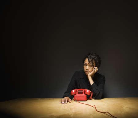 Trauriges Geschäftsfrauwartetelefon, um zu rufen