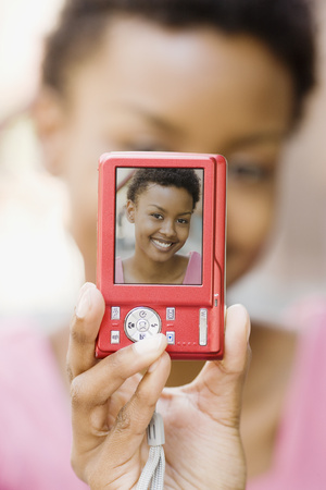 African woman taking self-portrait with digital camera