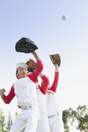 Multi-ethnic boys in baseball uniforms jumping to catch baseball LANG_EVOIMAGES