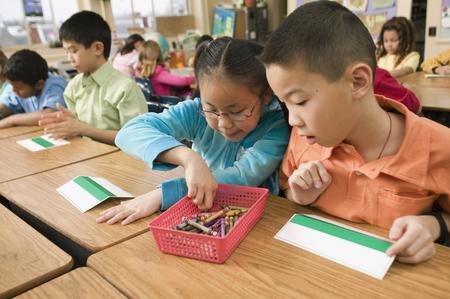 Asian school children making name cards