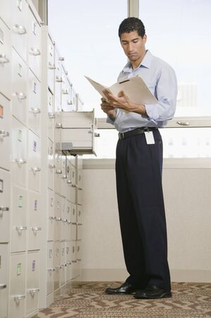 Mixed race businessman looking at files