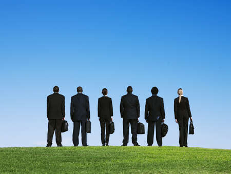 Business people standing outdoors in grass with briefcases LANG_EVOIMAGES