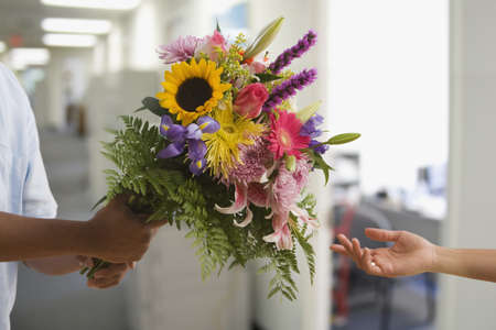 Man holding fresh bouquet of flowers LANG_EVOIMAGES