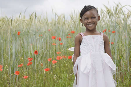African girl wearing fairy costume in grass LANG_EVOIMAGES
