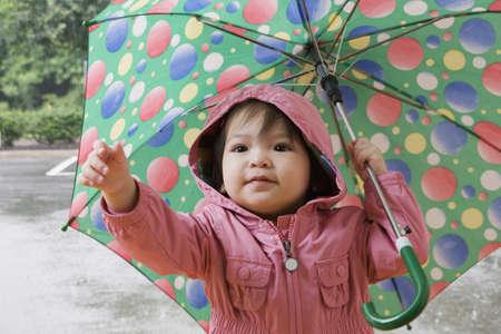 Mixed race girl holding umbrella