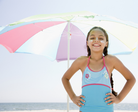 Hispanic girl with sunscreen under umbrella on beach LANG_EVOIMAGES
