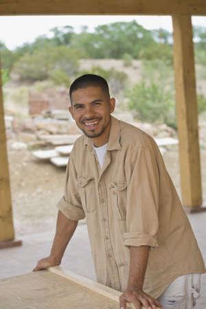 Hispanic man smiling at construction site