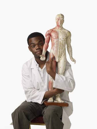 African chiropractor holding anatomical model LANG_EVOIMAGES