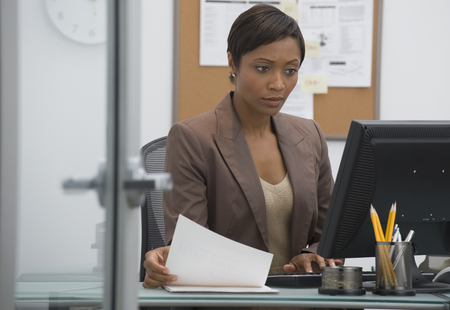 Worried African businesswoman working at computer LANG_EVOIMAGES