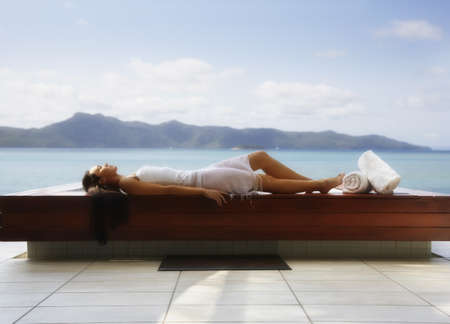 Pacific Islander woman laying next to water LANG_EVOIMAGES