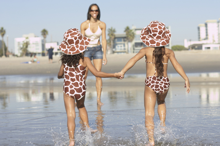 Young mixed race girls running to mother at beach