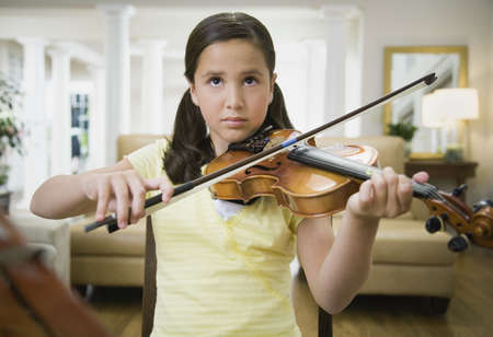 Girl playing violin indoors