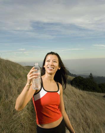 Asian woman holding water bottle on hillside