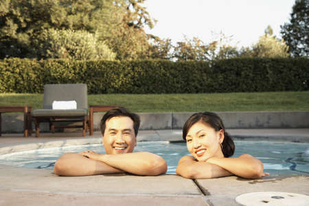 Asian couple leaning on edge of swimming pool