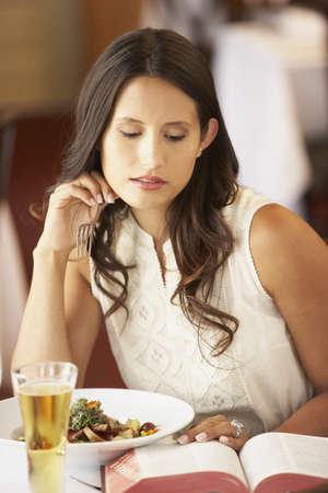 Hispanic woman reading at restaurant