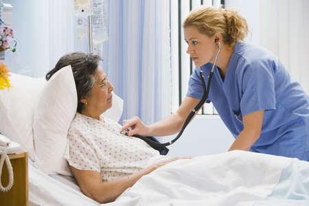 Female nurse using stethoscope on senior woman in hospital bed